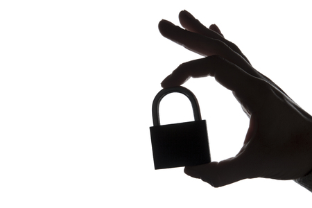 Silhouette of a hand holding a padlock on a plain white background. Security and privacy.