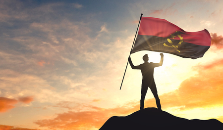 Angola flag being waved by a man celebrating success at the top of a mountain. 3D Rendering