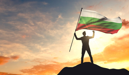 Bulgaria flag being waved by a man celebrating success at the top of a mountain. 3D Rendering