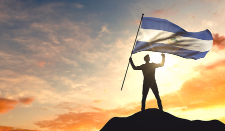 Nicaragua flag being waved by a man celebrating success at the top of a mountain. 3D Rendering