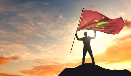 Vietnam flag being waved by a man celebrating success at the top of a mountain. 3D Rendering Stock Photo