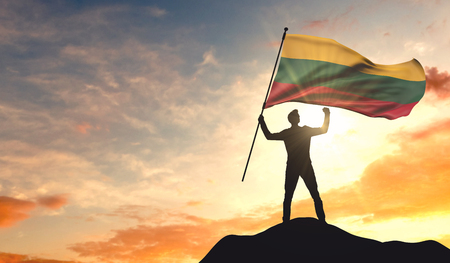 Lithuania flag being waved by a man celebrating success at the top of a mountain. 3D Rendering 版權商用圖片