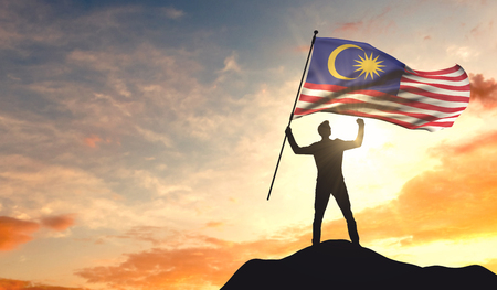 Malaysia flag being waved by a man celebrating success at the top of a mountain. 3D Rendering