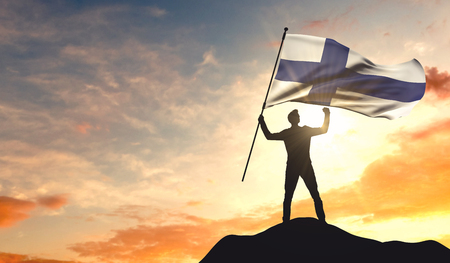 Finland flag being waved by a man celebrating success at the top of a mountain. 3D Rendering