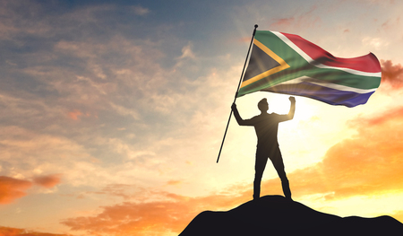 South Africa flag being waved by a man celebrating success at the top of a mountain. 3D Rendering