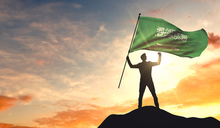 Saudi Arabia flag being waved by a man celebrating success at the top of a mountain. 3D Rendering