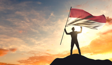 Indonesia flag being waved by a man celebrating success at the top of a mountain. 3D Rendering 스톡 콘텐츠 - 98928064