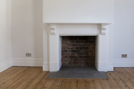 Victoriran wooden fireplace surround with white walls