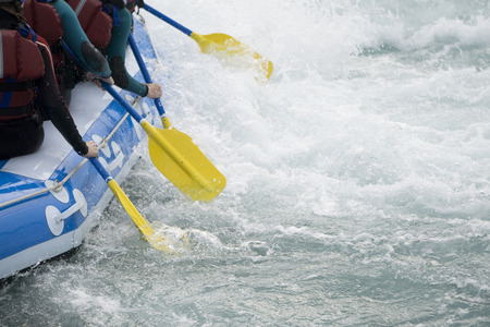 Close up of a team of people rafting on whitewater rapids