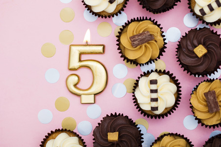 Number 5 gold candle with cupcakes against a pastel pink background