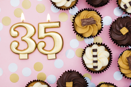 Number 35 gold candle with cupcakes against a pastel pink background