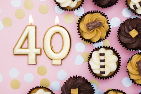 Number 40 gold candle with cupcakes against a pastel pink background Stock Photo