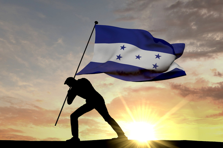 Honduras flag being pushed into the ground by a male silhouette. 3D Rendering Stock Photo