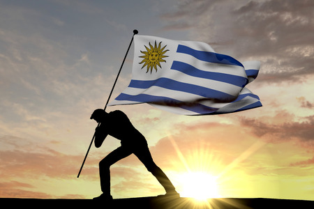 Uruguay flag being pushed into the ground by a male silhouette. 3D Rendering Stock Photo