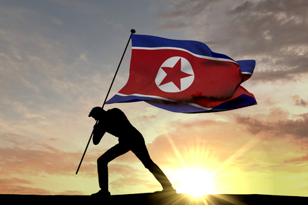 North Korea flag being pushed into the ground by a male silhouette. 3D Rendering
