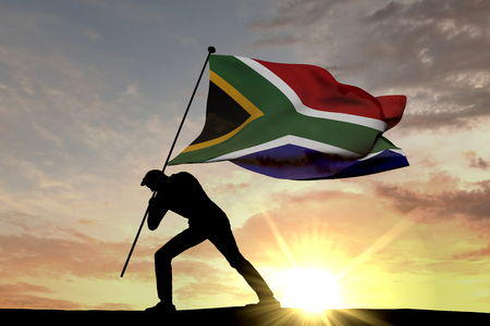 South Africa flag being pushed into the ground by a male silhouette. 3D Rendering Stock Photo