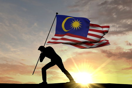 Malaysia flag being pushed into the ground by a male silhouette. 3D Rendering