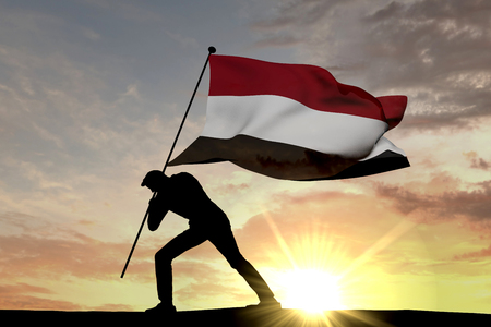 Yemen flag being pushed into the ground by a male silhouette. 3D Rendering Stock Photo