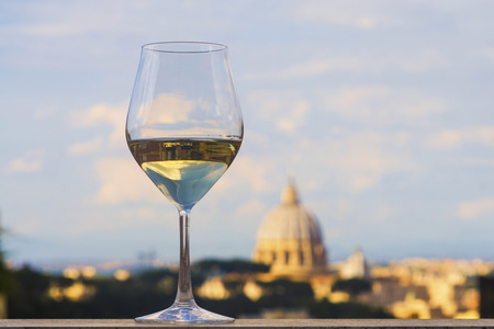 Glass of Italian white wine with St Peter's basilica, Rome, in the background