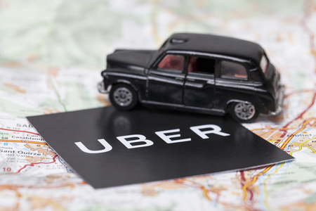 London, UK - MARCH 23rd 2017: A photograph of the Uber logo with a black London style taxi toy car. Uber is a popular taxi style transport service application, founded in 2009