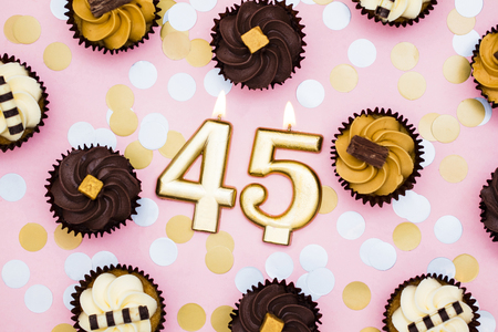 Number 45 gold candle with cupcakes against a pastel pink background
