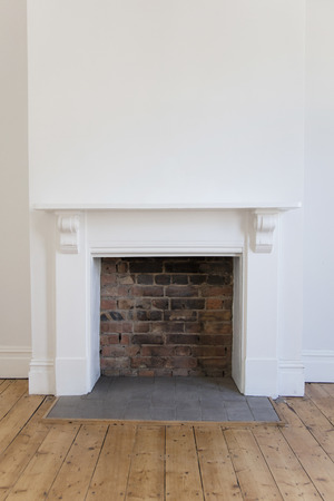 Victoriran wooden fireplace surround with white walls and wooden floor Banco de Imagens