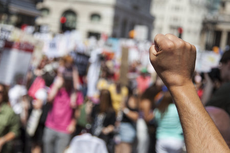 A raised fist of a protestor at a political demonstration Stock Photo