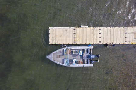 Aerial birdseye view of a speed boat at a pier.