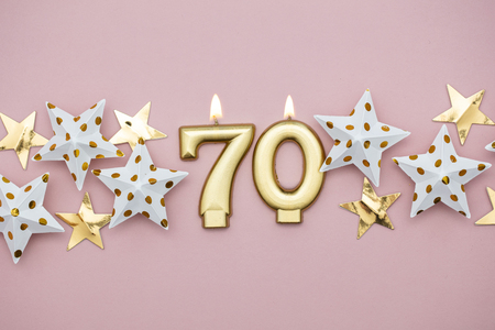 Number 70 gold candle and stars on a pastel pink background