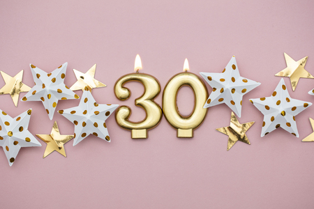 Number 30 gold candle and stars on a pastel pink background