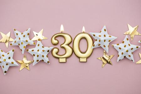 Nummer 30 gouden kaars en sterren op een pastelroze achtergrond