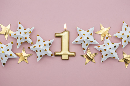 Number 1 gold candle and stars on a pastel pink background