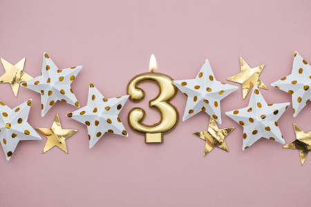 Number 3 gold candle and stars on a pastel pink background Archivio Fotografico