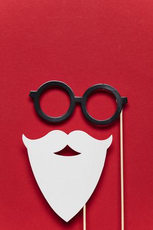 Santa barba blanca y gafas sobre un fondo rojo. Foto de archivo