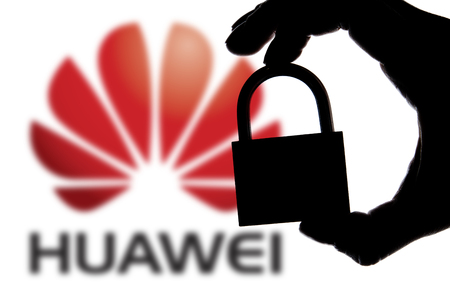 LONDON, UK - November 29th 2018: Huawei security issues. Silhouette of a hand holding a padlock in front of the Huawei icon. Imagens - 113414124