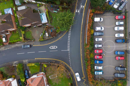 Aerial view of vehicles travelling on roads in the suburbs in a town in the UK