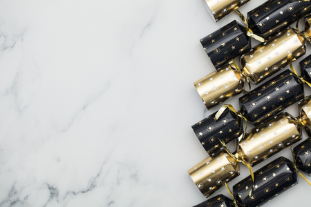 Christmas crackers. luxury gold and black festive crackers on a marble background