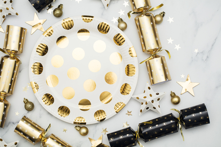 Festive Christmas party place setting with gold plate, cracker and decorations