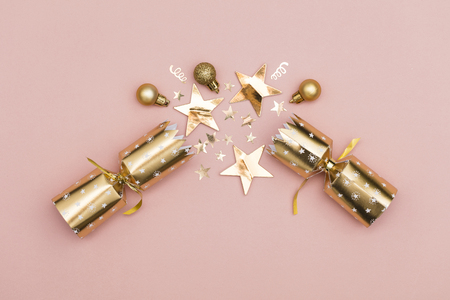 Christmas crackers. luxury gold festive cracker on a pastel pink background 스톡 콘텐츠