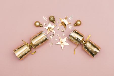 Christmas crackers. luxury gold festive cracker on a pastel pink background Foto de archivo