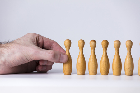 Hand selecting a wooden figure. Business leadership concept
