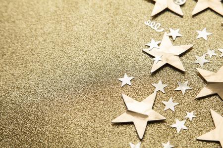 Goldstern funkeln Partykonfetti auf einem goldenen Glitzerhintergrund Standard-Bild