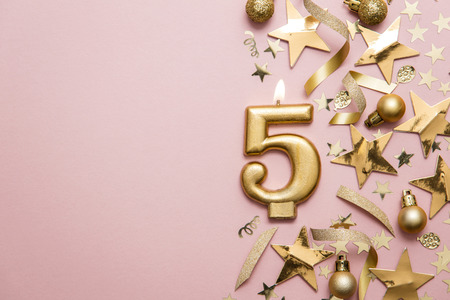 Number 5 gold celebration candle on star and glitter background Banco de Imagens