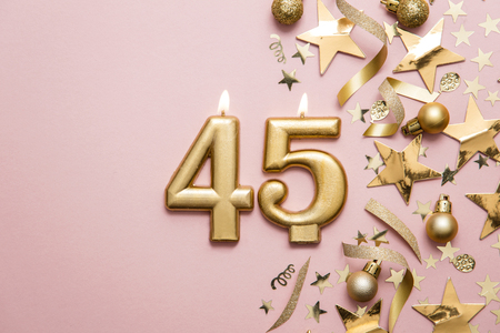Number 45 gold celebration candle on star and glitter background