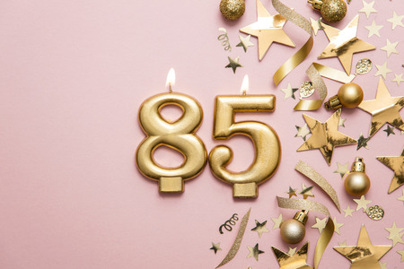 Number 85 gold celebration candle on star and glitter background