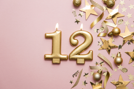 Number 12 gold celebration candle on star and glitter background Stock Photo