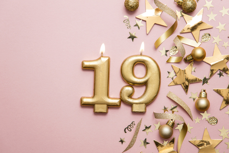 Number 19 gold celebration candle on star and glitter background Stock Photo
