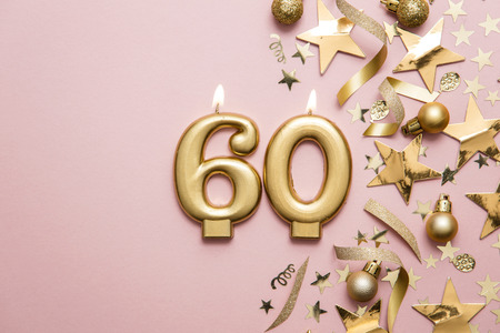 Number 60 gold celebration candle on star and glitter background
