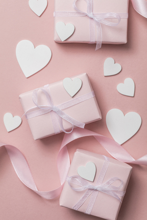 Pink valentine gift with white hearts on a pastel pink background 写真素材