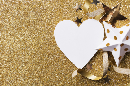 White heart shape on a golden glitter backgrond